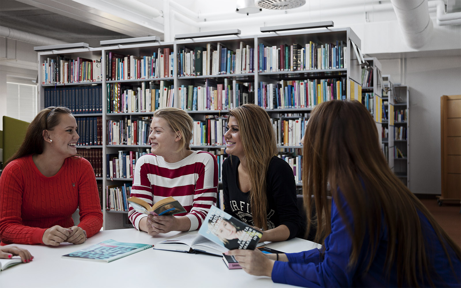 Students of the Sågbäcksgymnasiet in the library illuminated by natural light