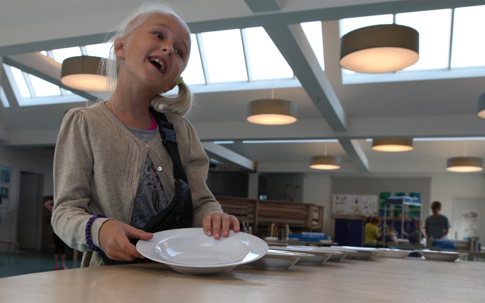 Young student in cafeteria illuminated with skylight and artificial lighting